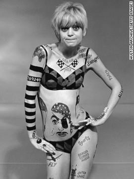Απεικονίζεται μία ξανθιά γυναίκα, φοράει ένα μπικίνι μαγιό με γεωμετρικά σχήματα και το σώμα της έχει τατουάζ