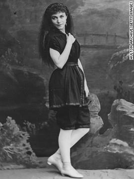 Απεικονίζεται μία γυναίκα με το μαγιό φόρεμα. Έχει μανίκι και τελειώνει λίγο πιο πάνω από το γόνατο