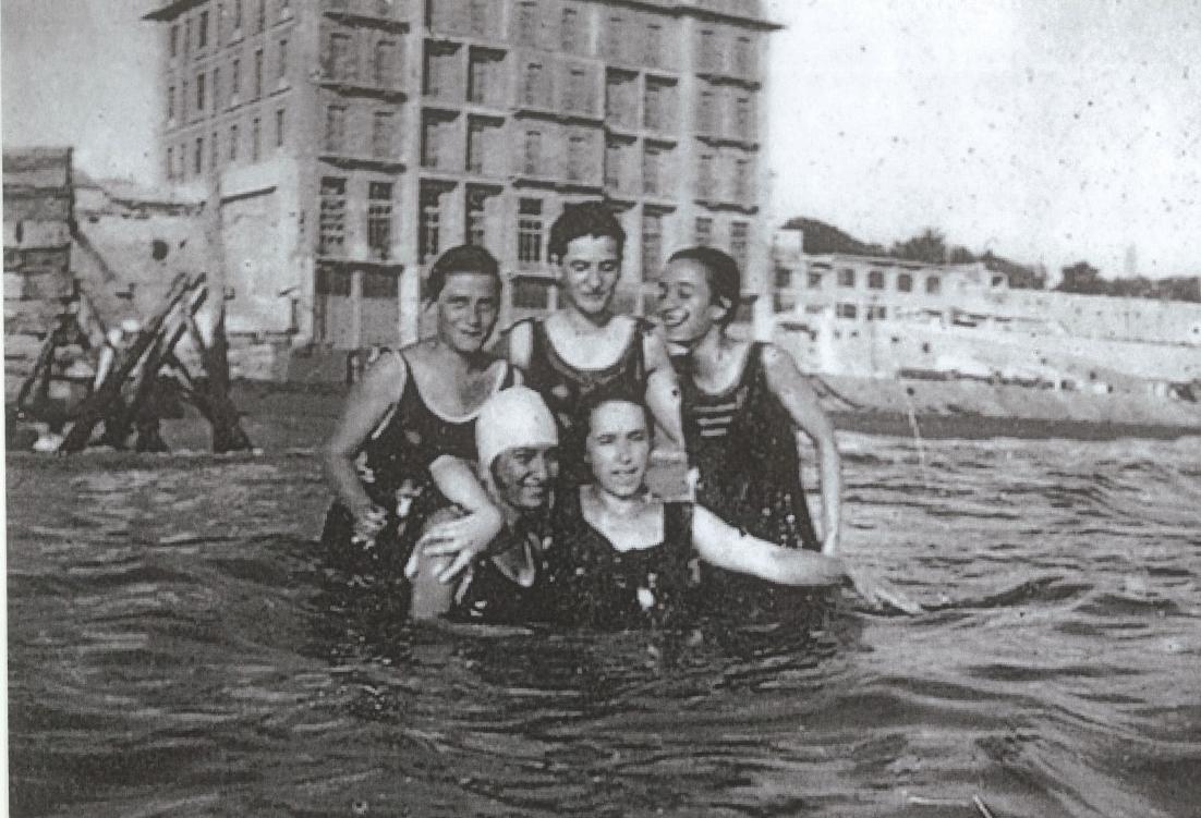 Απεικονίζονται πέντε γυναίκες αγκαλιασμένες μέσα στη θάλασσα