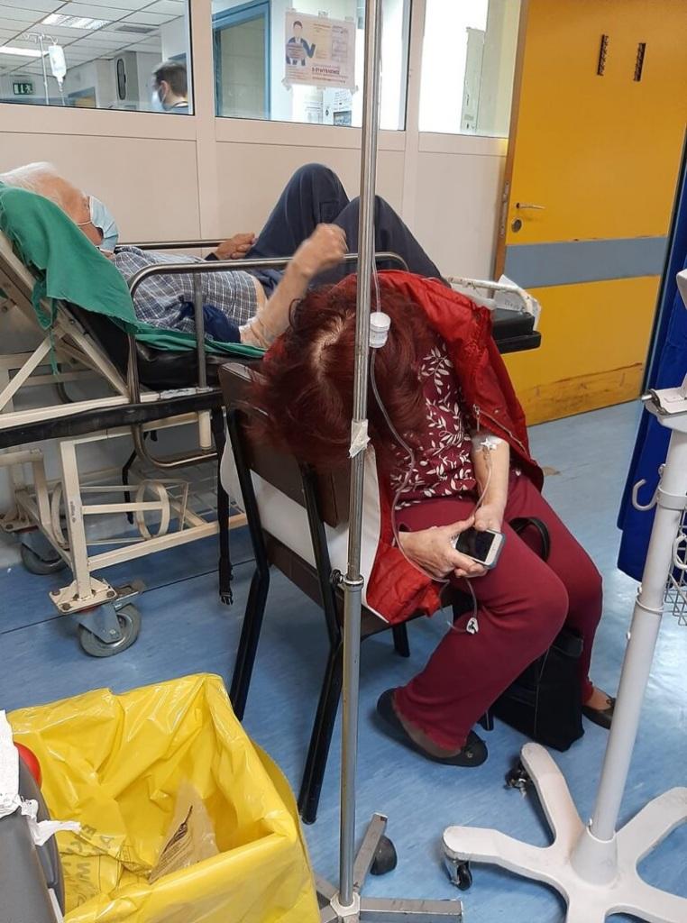 Η ηλικιωμένηγυναίκακαθισμένη σε καρέκλα μέσα σε θάλαμο του νοσοκομείου, γέρνει ταλαιπωρημένη το κεφάλι της