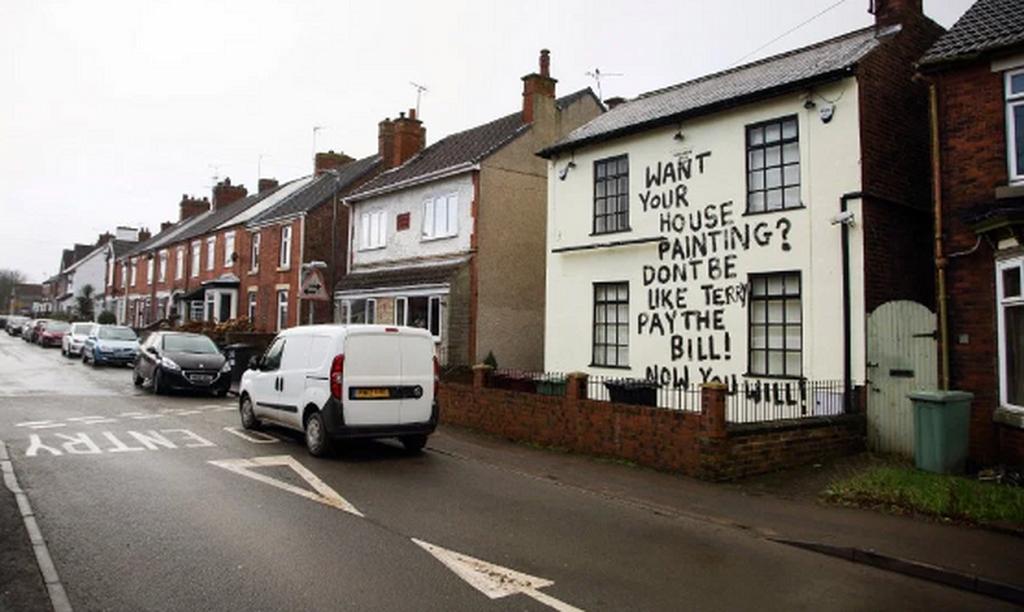 Ο ελαιοχρωματιστής έγραψε με μεγάλα μαύρα γράμματα στον τοίχο του σπιτιού.png